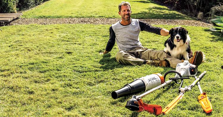A man and his dog sitting in a back yard with his Stihl power tools